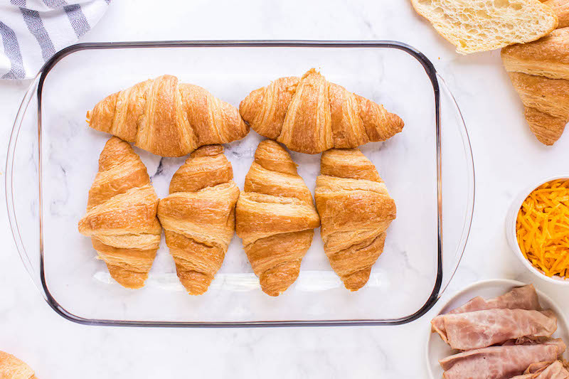 6 croissants in a glass pan.
