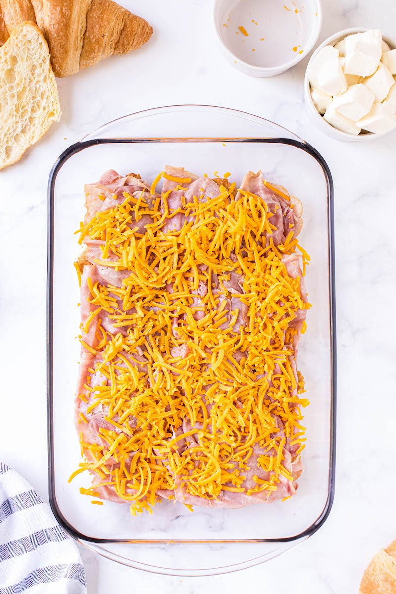 Deli ham topped with shredded cheese in a pan.