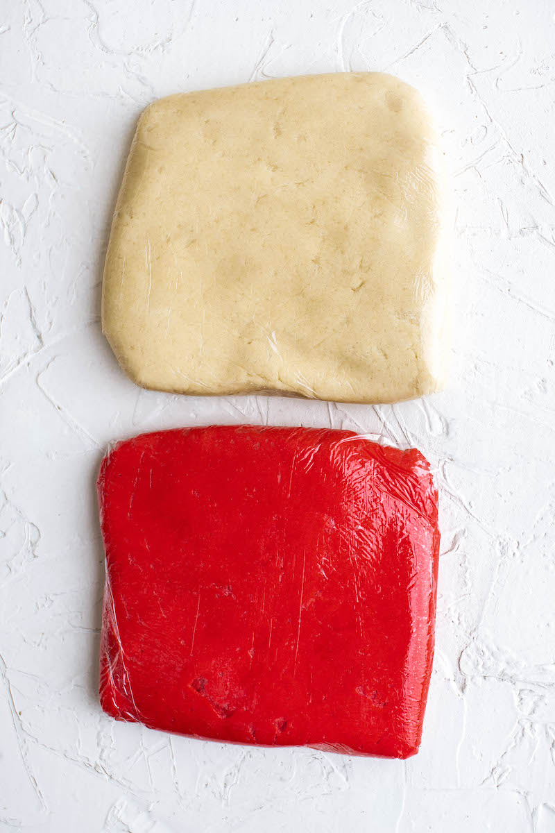 Red cookie dough next to uncolored cookie dough.