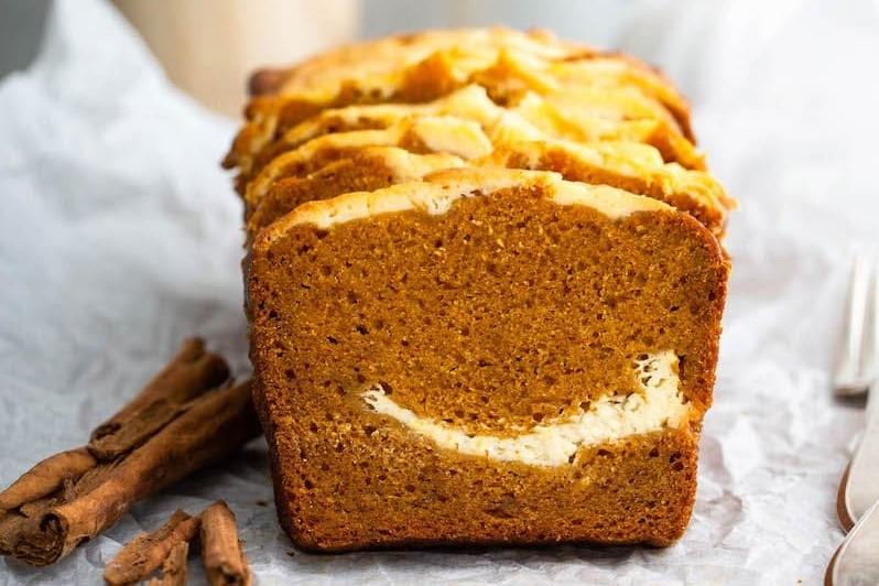 A sliced loaf of pumpkin cream cheese bread