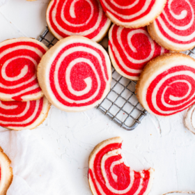 Overhead image of pinwheel cookies on a cookie cooling rack and marble countertop.