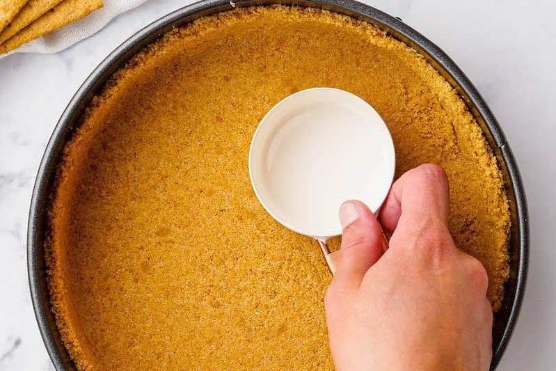 Graham cracker crust being pressed into a springform pan