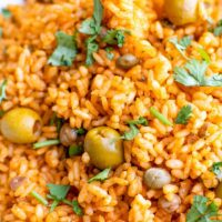 A close up shot of arroz con gandules shoes cilantro, olives, peas and rice.