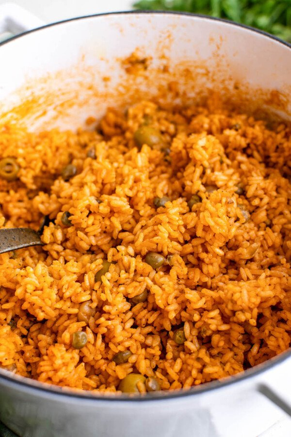Rice is being stirred in a large skillet.