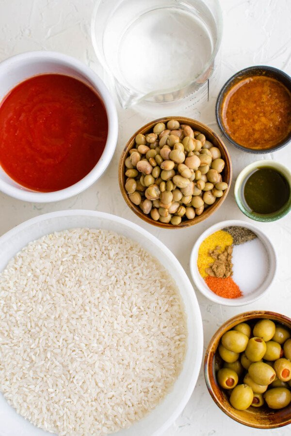 The ingredients for this rice dish are separated in bowls on a white surface.