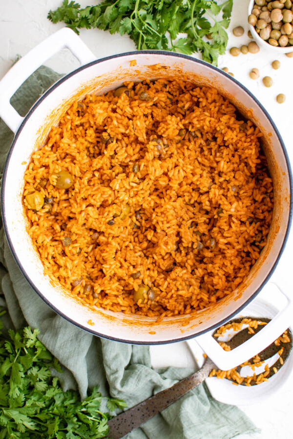 Freshly cooked arroz con gandules is in a large white pot.