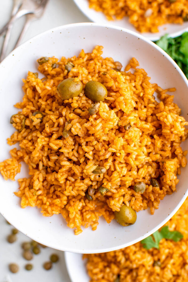 A helping of arroz con gandules is served on a white plate.