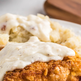 Up close image of chicken fried chicken with gravy on top on a white plate.