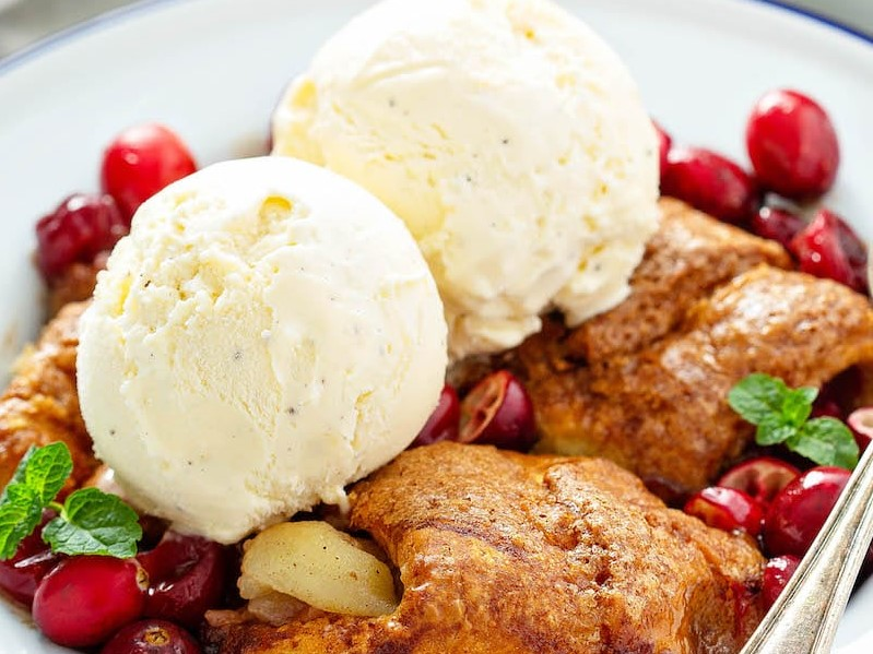 Cranberry Apple Dumplings in a bowl with vanilla ice cream