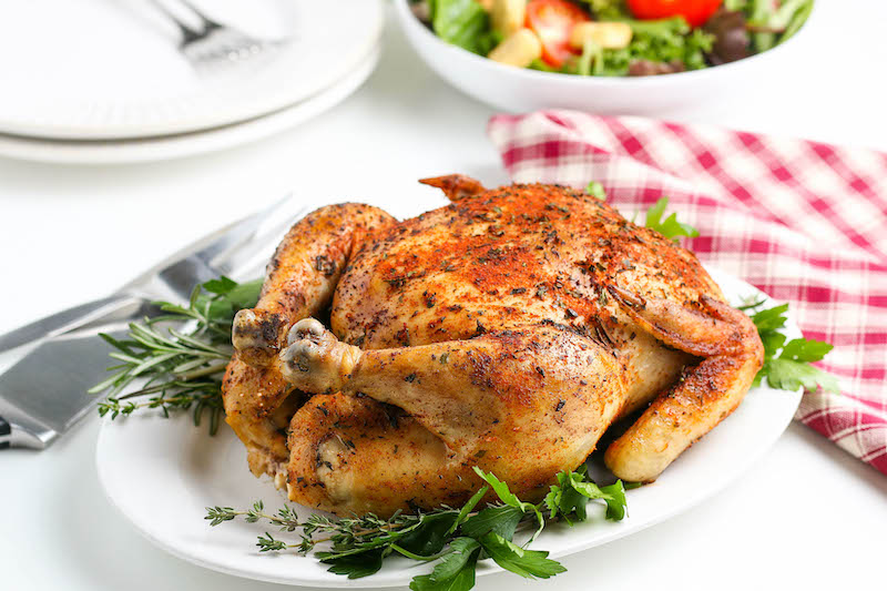 Whole chicken on a plate of greens.