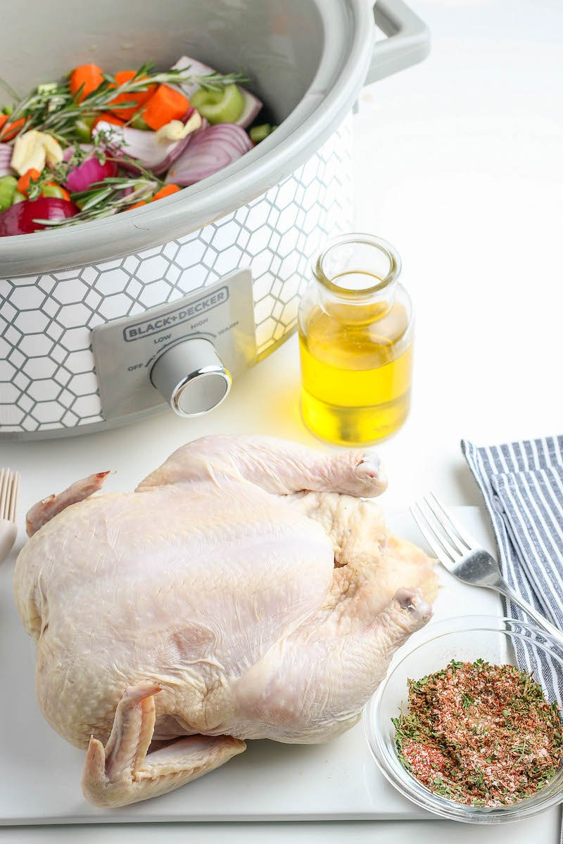Uncooked whole chicken next to bowl of seasoning.