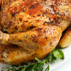 Close up image of crockpot whole chicken on a white plate.