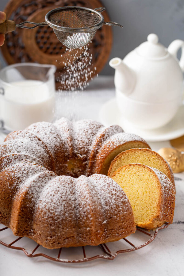 Powdered sugar is sprinkled on top of the fully baked bundt cake.