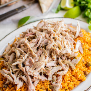 Shredded pernil is served over Spanish rice, ready to be eaten.