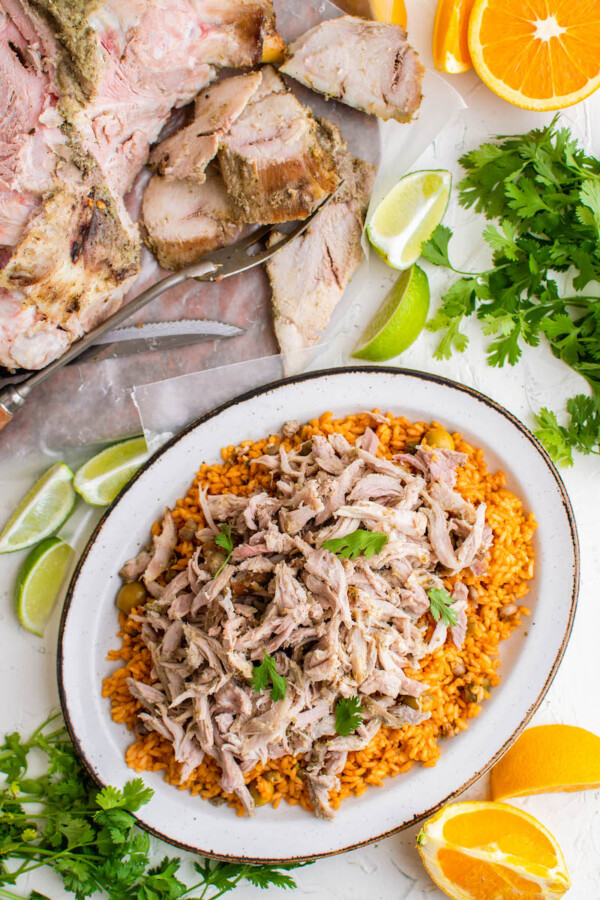 Puerto Rican Pernil is served on top of arroz con gandules.