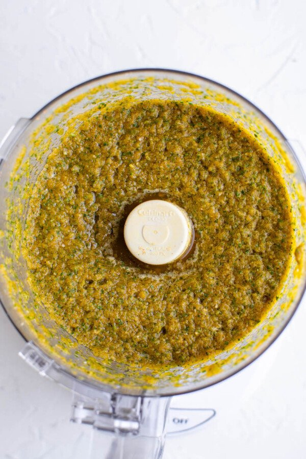 The ingredients and spices have been fully blended together, creating a greenish mixture.