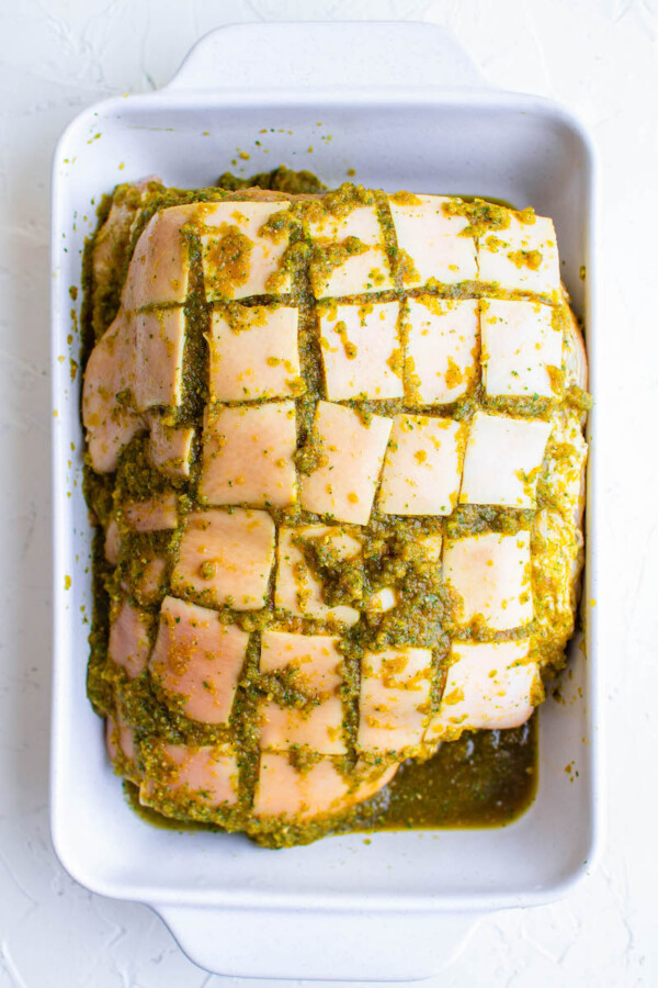 The skin of the pork is cut into symmetrical squares and covered with green marinade.