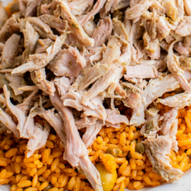 Shredded Pernil on a white plate with arroz con gandules.