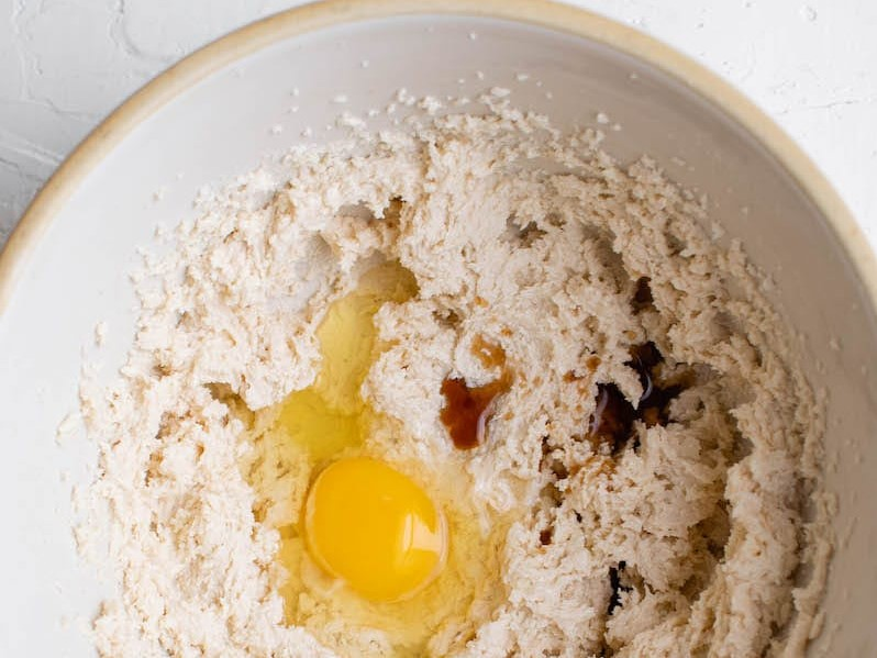 Top view of a mixing bowl with beaten butter and sugar with an egg and vanilla