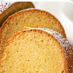 Up close image of rum bundt cake sliced into pieces with powdered sugar on top.
