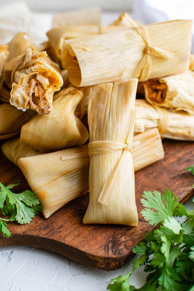 Tamales piled on a cutting board.