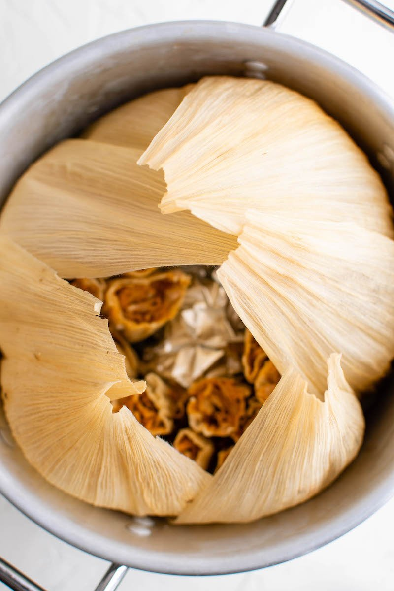 Pot of tamales lined with corn husks.