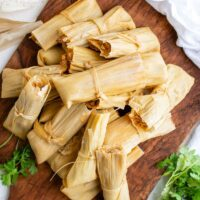 Pile of tamales on a wooden board.