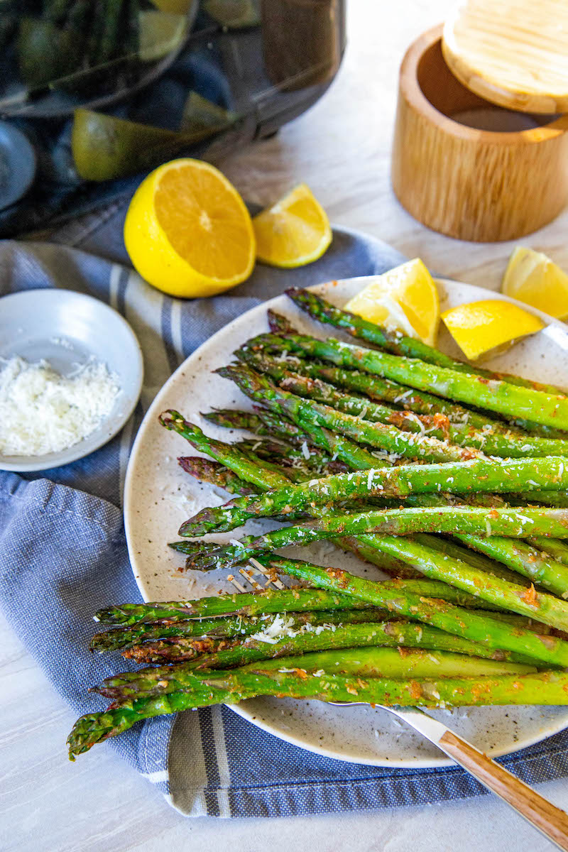 Plate of air fryer asparagus with lemon wedges.
