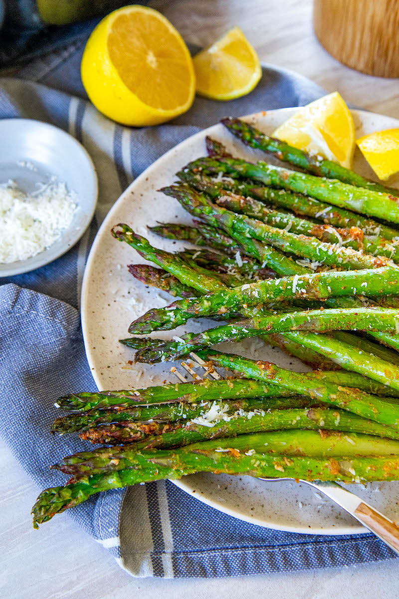 Pile of asparagus on a plate.