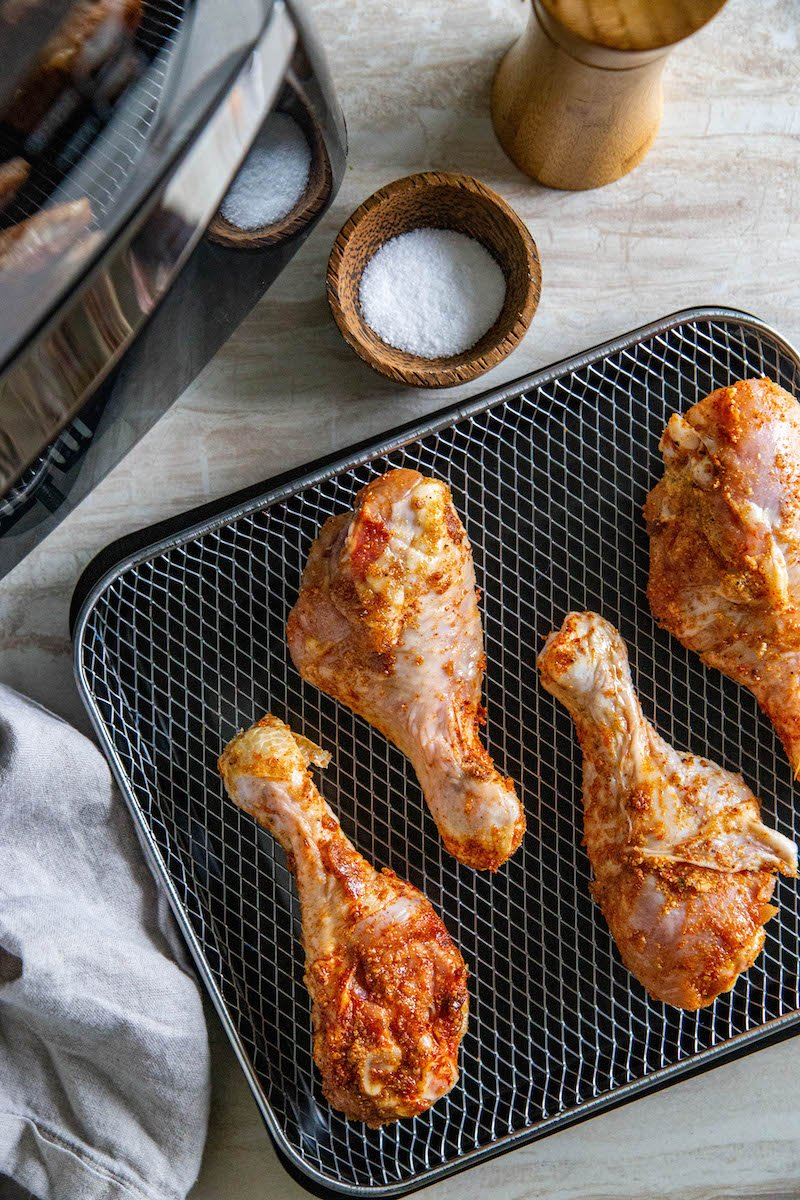 Uncooked chicken drumsticks on an air fryer tray.
