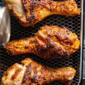 Overhead image of 4 chicken legs on an air fryer basket.