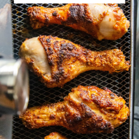 Overhead image of chicken legs coming out of an air fryer.