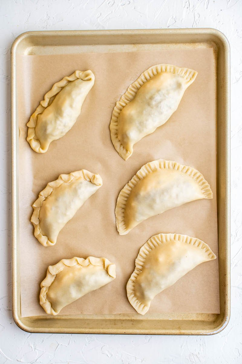 Uncooked empanadas on a tray.