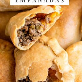 Up close image of a beef empanada torn in half sitting on top of other empanadas.