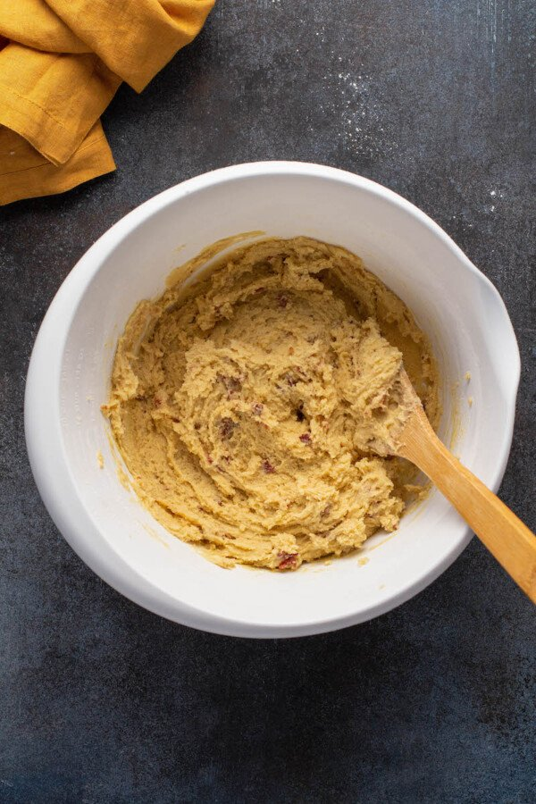 A wooden mixing spoon is stirring the dough.