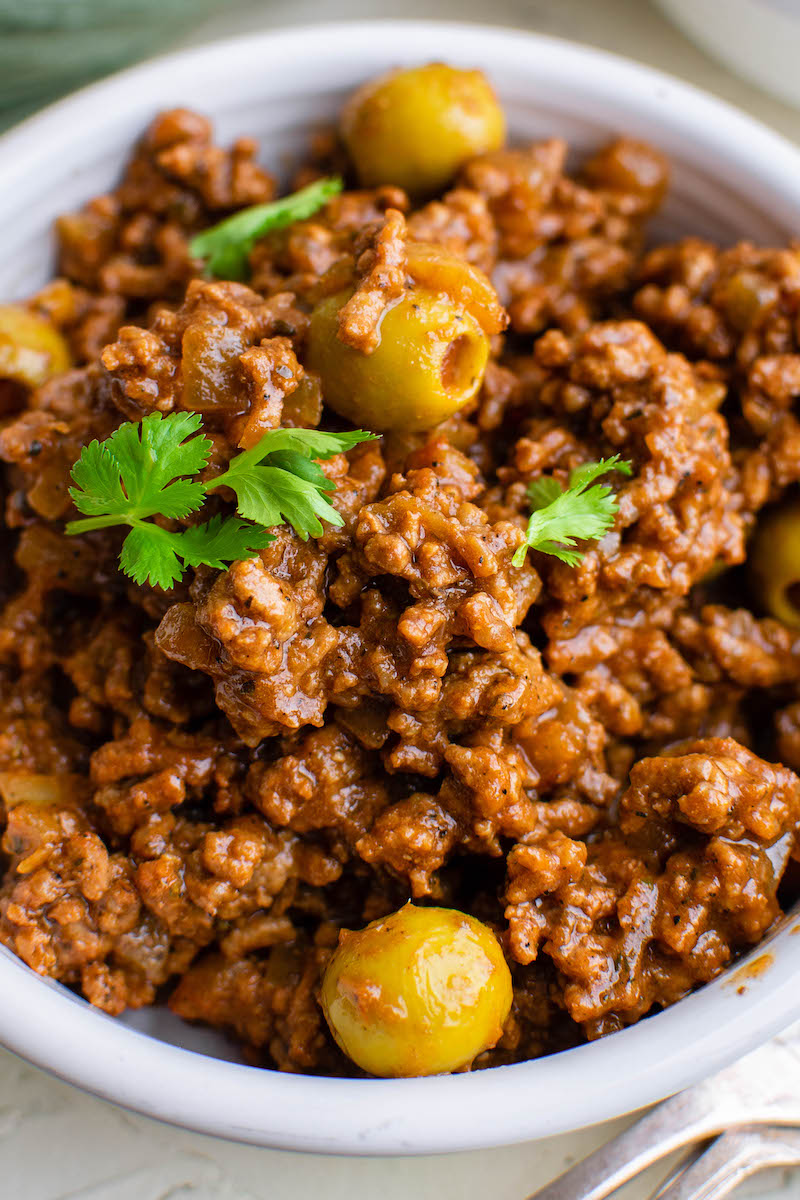 Up close image of picadillo in a white bowl with olive sand cilantro on top.