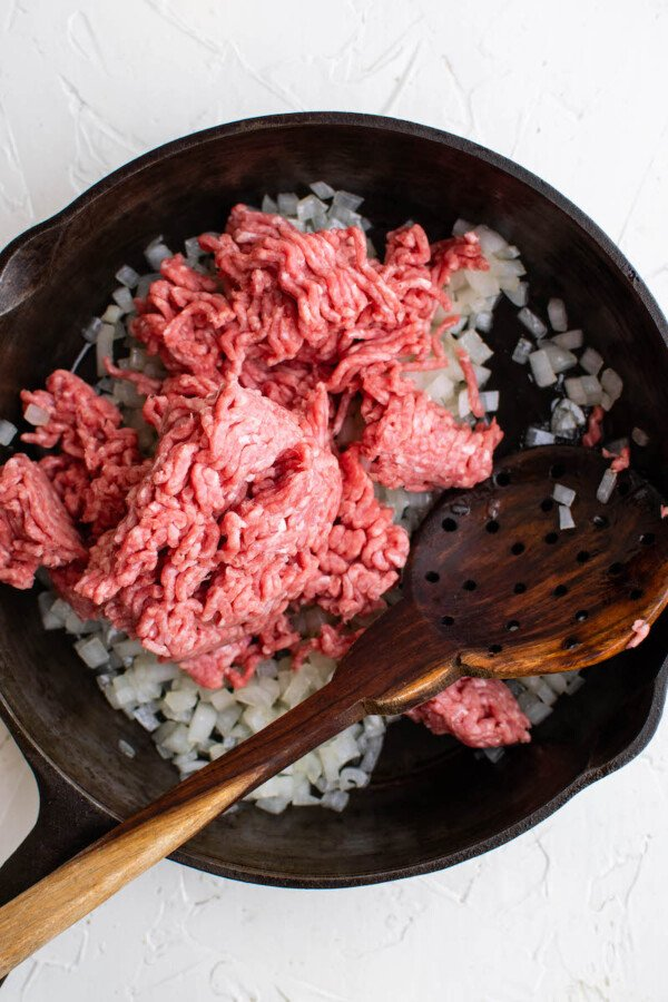 Diced onion and uncooked ground beef in a pan.