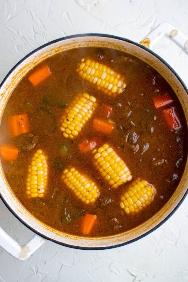 Beef broth and corn cobs in a soup pot.