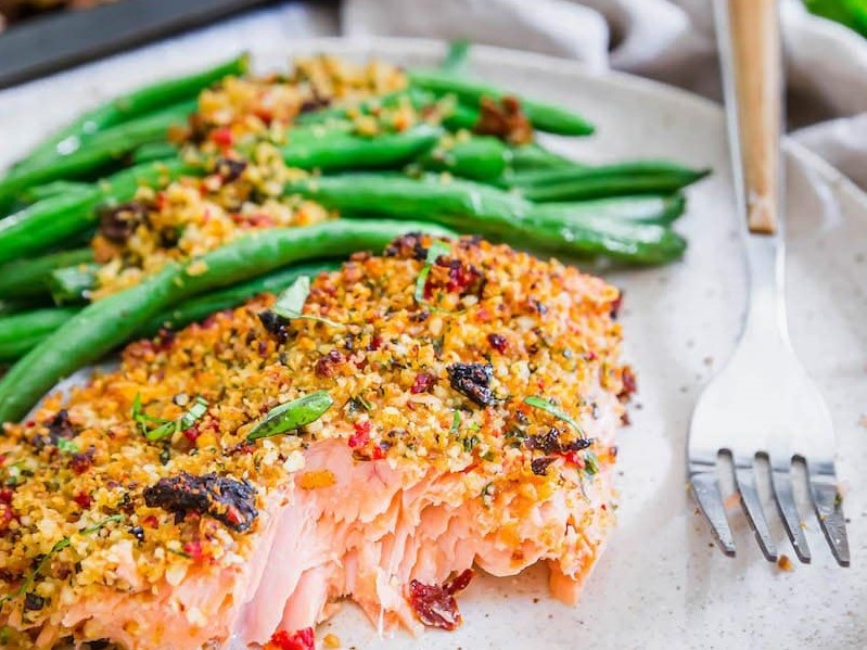 A serving of Sun-Dried Tomato Parmesan Crusted Salmon with Green Beans on a plate