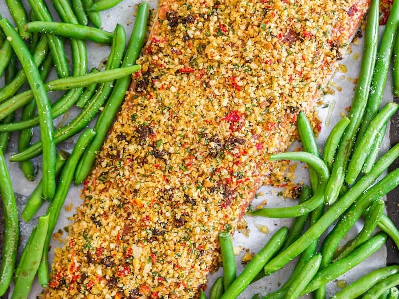 Uncooked Sun-Dried Tomato and Parmesan Crusted Salmon with green beans scattered around on a baking sheet