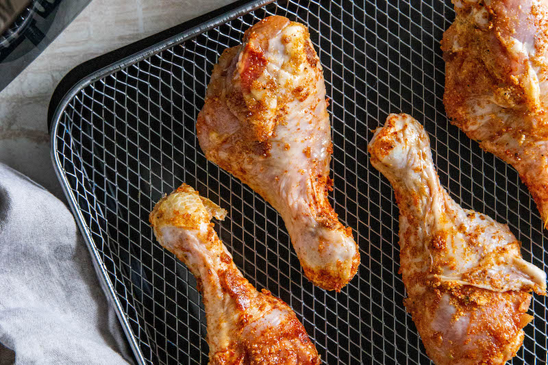 Chicken legs on an air fryer tray before going into air fryer.