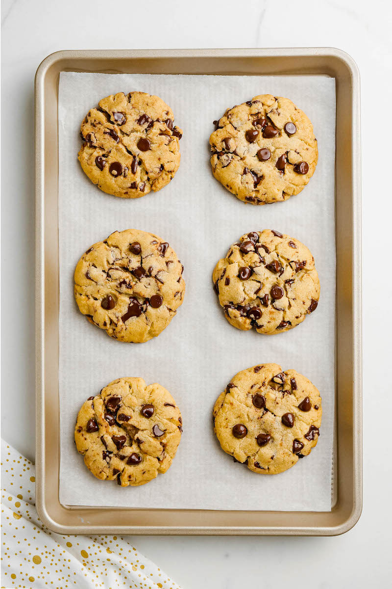 Baked chocolate chip cookies on a pan.