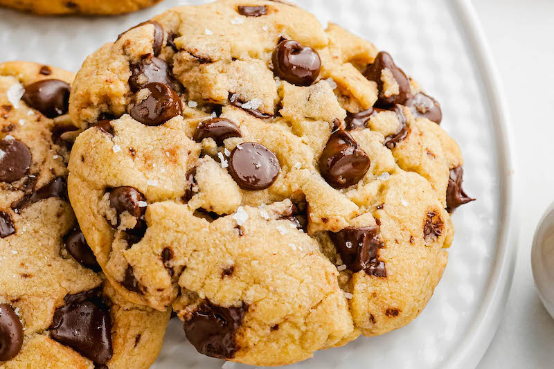 Up close image of brown butter chocolate chip cookies with sea salt sprinkled on top on a white plate.
