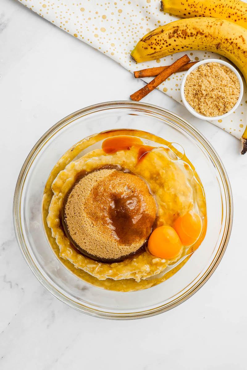 Brown sugar, banana, and eggs in a mixing bowl.