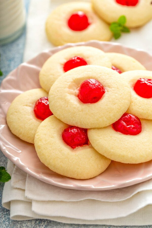 Cherry Almond Shortbread Cookies stack don a pink plate with a white napkin.