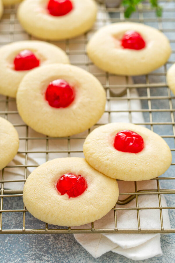 Almond shortbread cookies with a cherry in the center on a cooling rack.