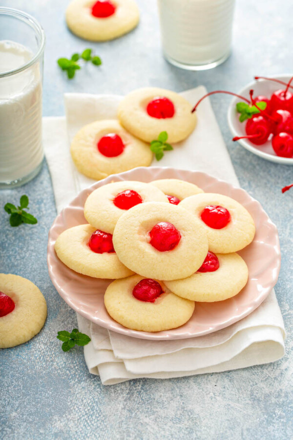 A pink plate filled with shortbread cookies with cherries on a white napkin with glasses of milk.
