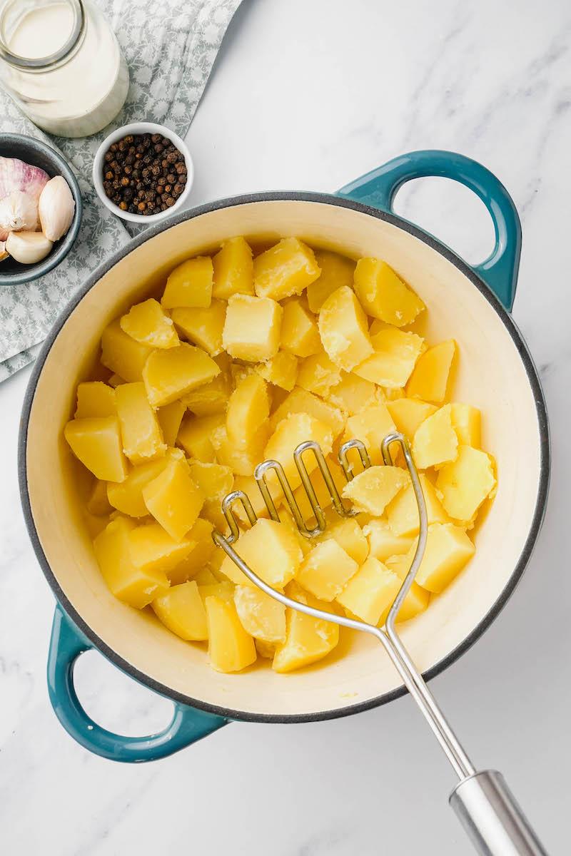 Potato mashed in a pot of chopped potatoes.