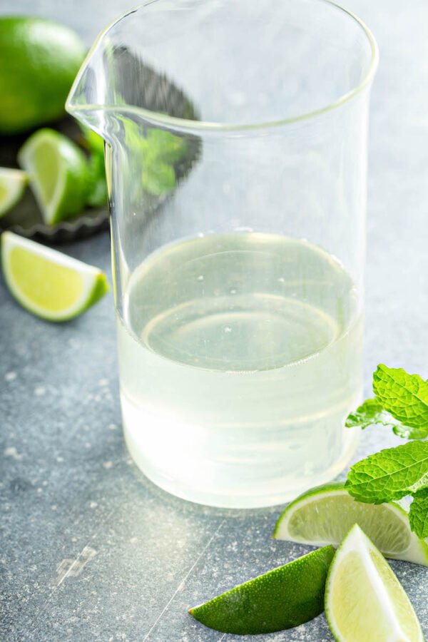 Mojito syrup in a large pitcher with limes and mint.