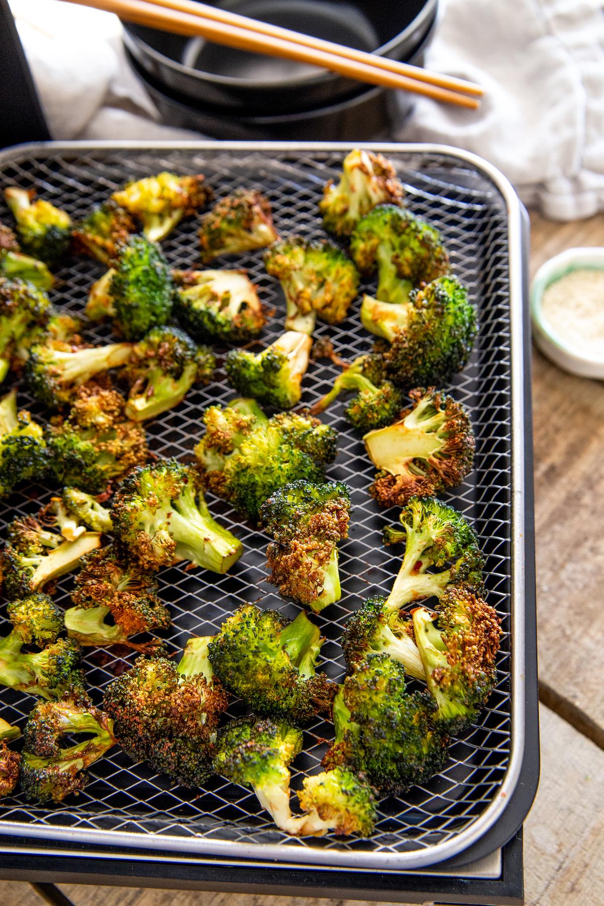 Broccoli florets on an air fryer tray.